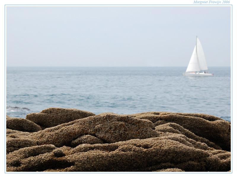 zee met bootje en rotsen in bretagne, frankrijk
